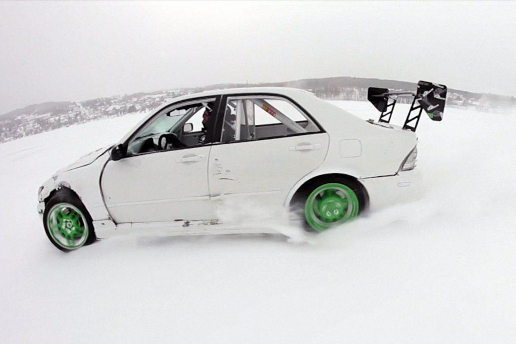 A modified white Lexus IS300 sedan drifting on a frozen lake