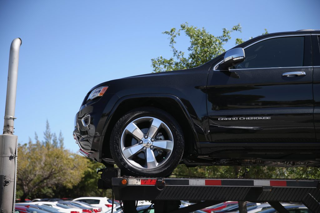 A Jeep Grand Cherokee on a transport truck to its destination.