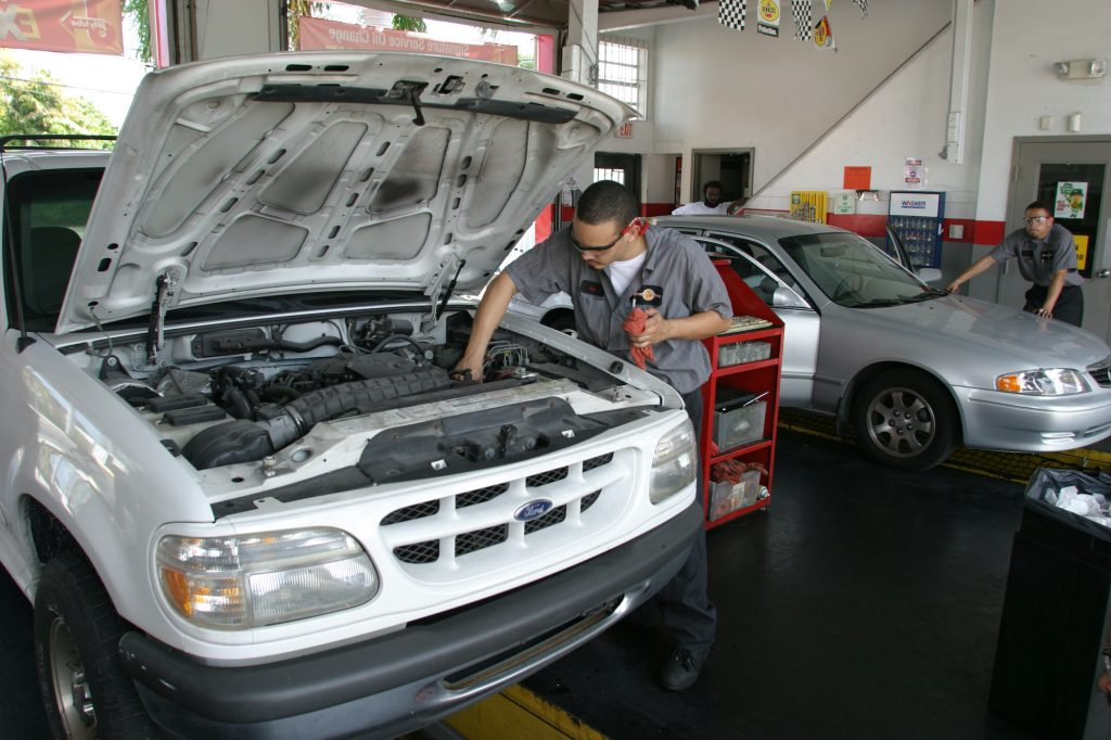 A mechanic changes the oil on a car.