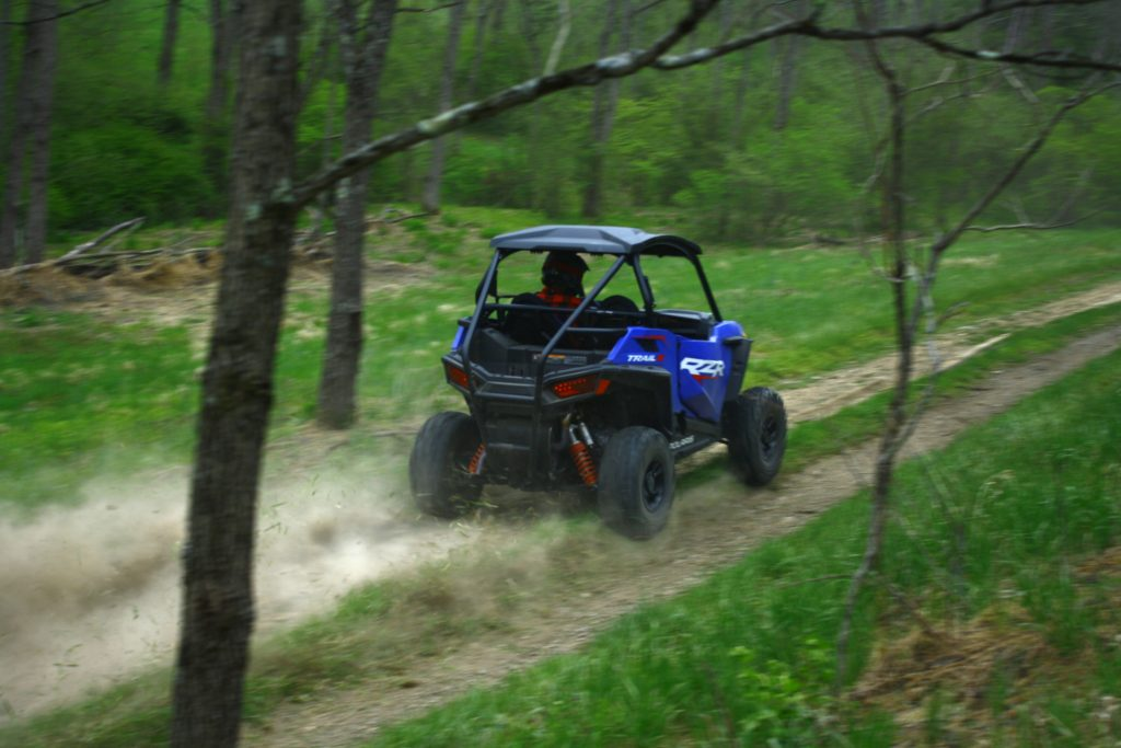 UTV buggy racing through the woods kicking up a ton of dust
