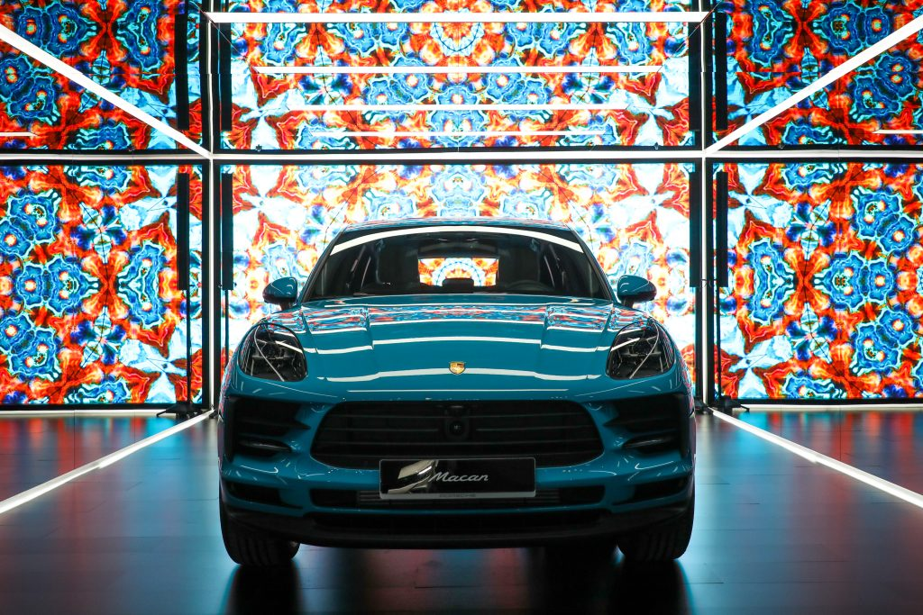 A baby blue Porsche Macan in a stained glass photobooth at it's release in Seoul.