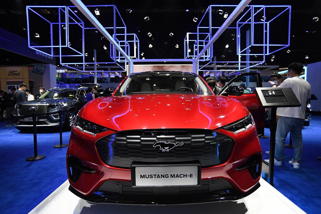A red 2021 Ford Mustang Mach-E sits on the floor of a car show. The Mach-E is one of Ford's new electric vehicles.