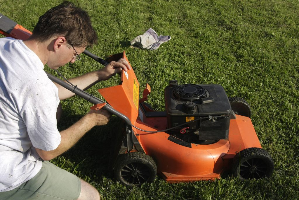 A man performing maintenance on a lawn mower