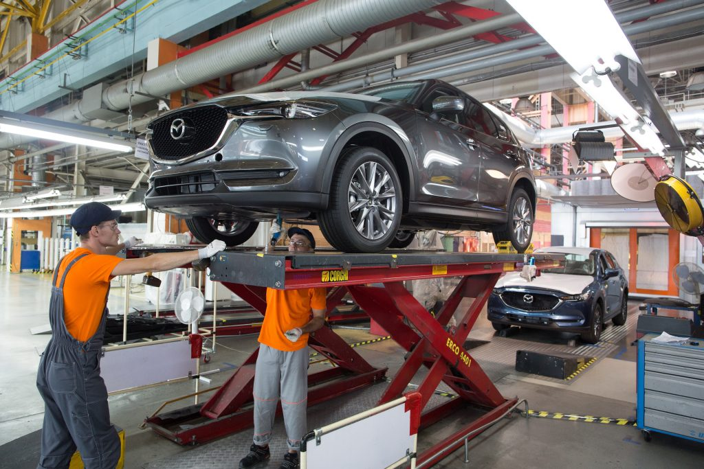 Workers affix parts to the underside of a gray Mazda CX-5 sports utility vehicle (SUV) on the assembly line at the Mazda Sollers Manufacturing Rus LLC plant