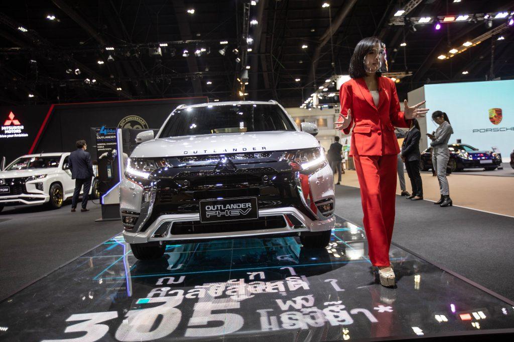 A model stands next to a silver Mitsubishi Outlander PHEV at the Mitsubishi stand during the 42nd Bangkok International Motor Show