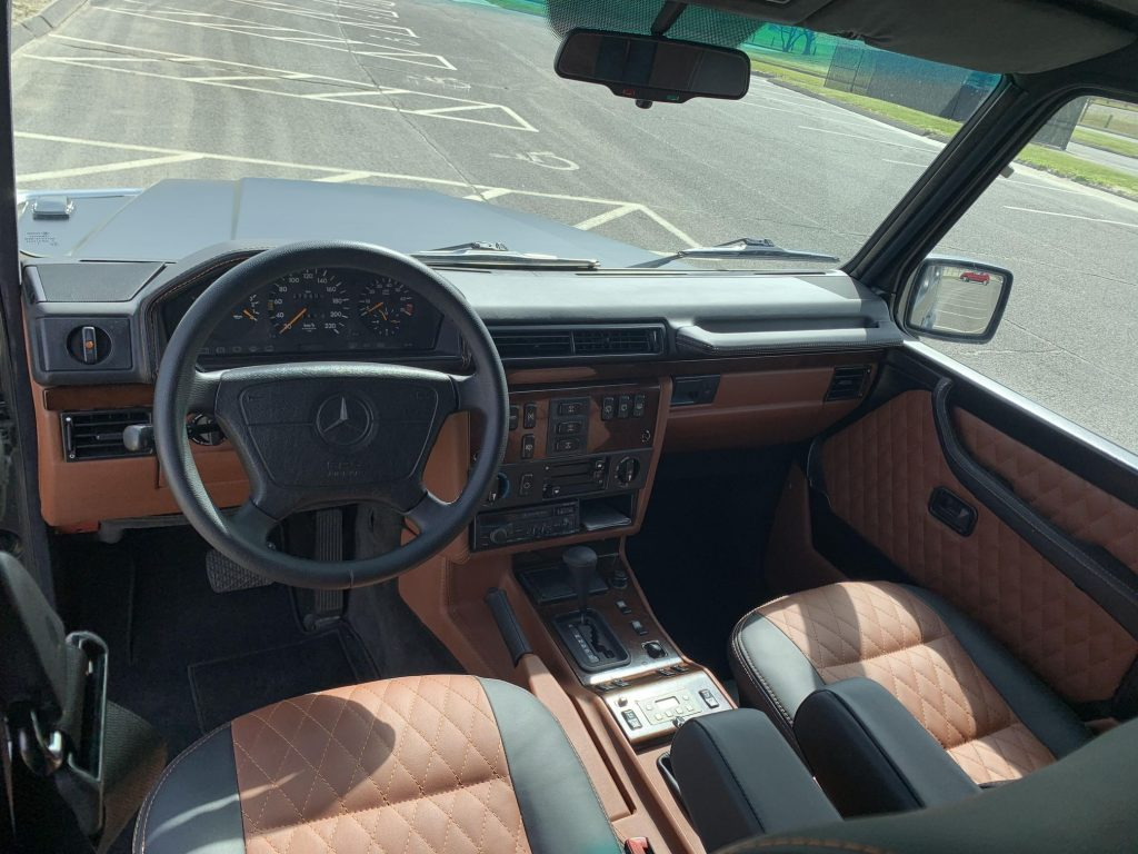 The brown-and-black-leather-upholstered front seats and wood-trimmed dashboard of a modified 1995 Mercedes-Benz G320