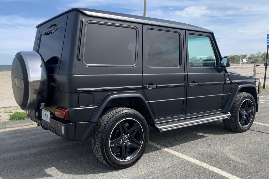 The rear 3/4 view of a modified matte-black 1995 Mercedes-Benz G320 on a beachside parking lot