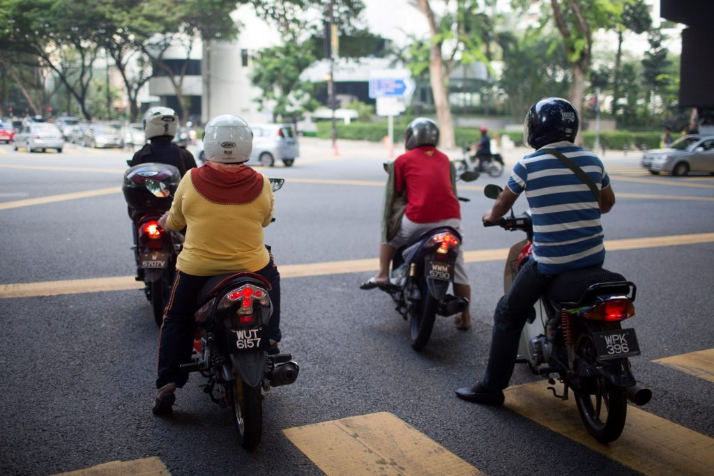 Motorcycle riders in Malaysia wait at a red light
