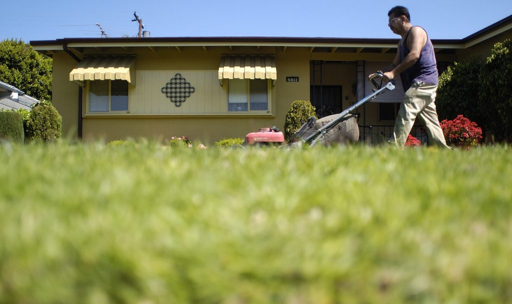 A man mowing a small yard.