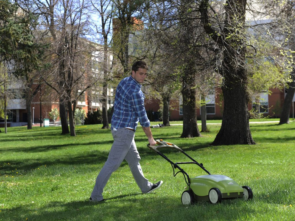 A man mowing the lawn with an electric lawn mower
