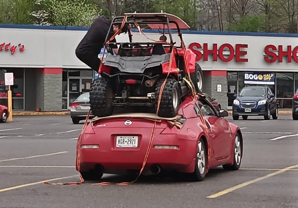 a red Nissan 350Z in a praking lot with a red side-by-side strapped onto the roof