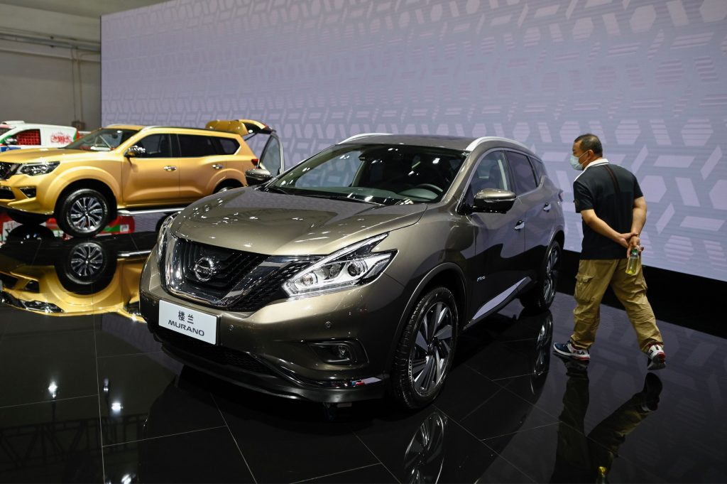 A man looks at a gray Nissan Murano car displayed at the Beijing Auto Show in Beijing