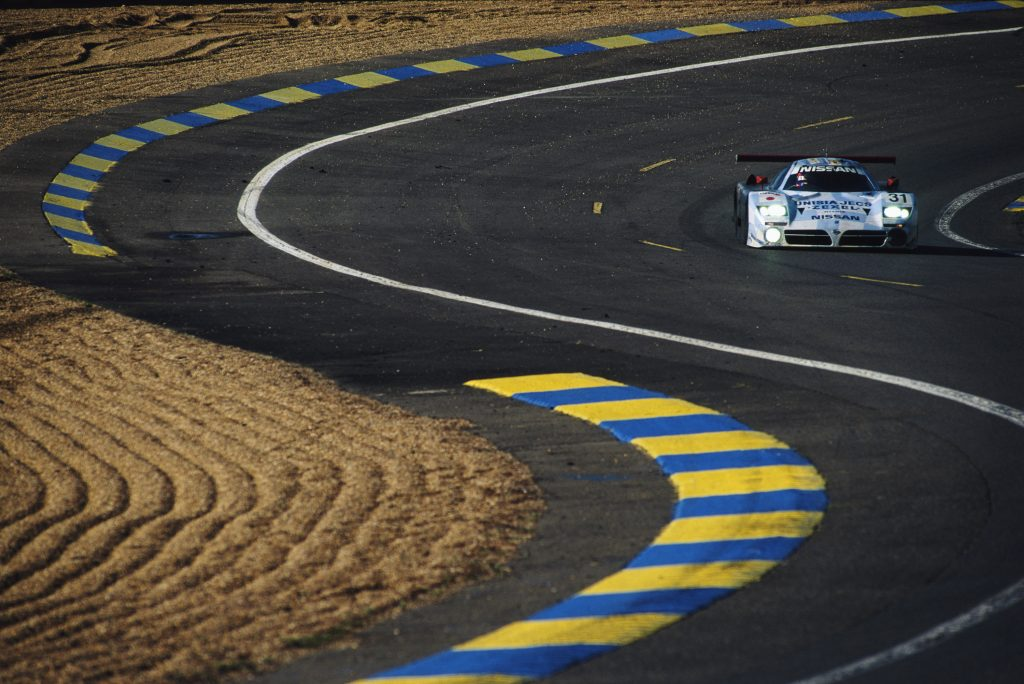 The Nissan R390 GT1 race car on a paved road