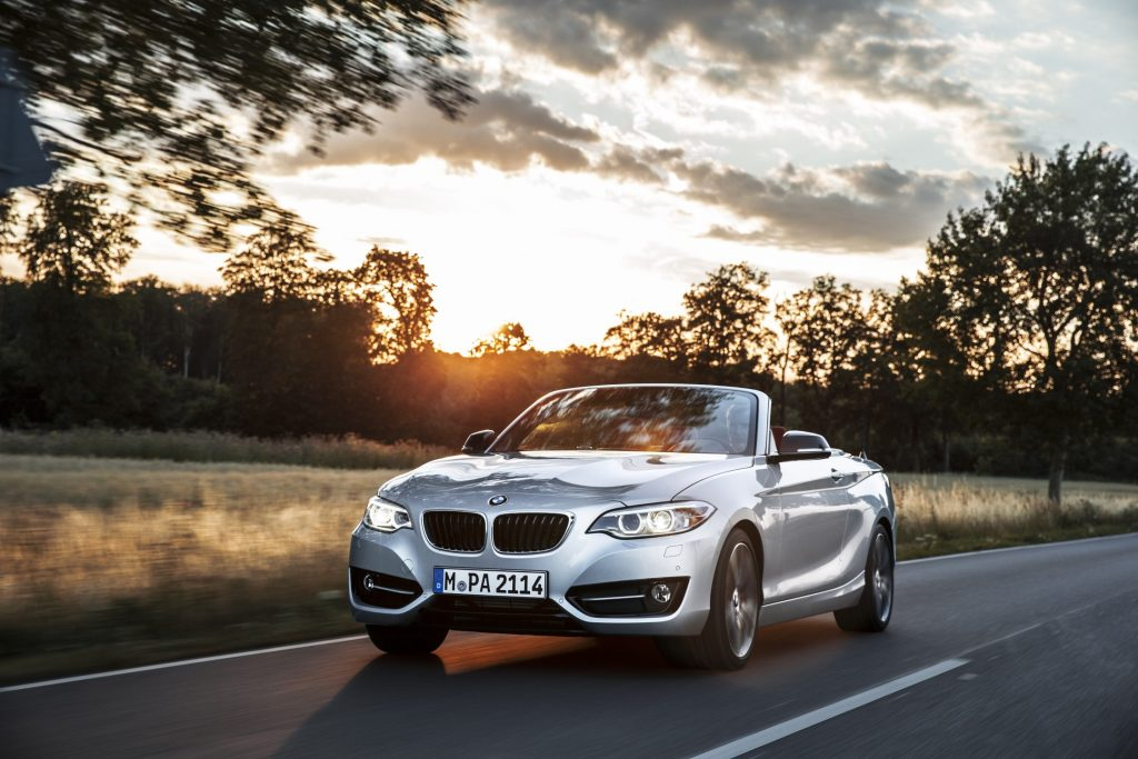 A silver 2 series convertible drives down a road at sunset photographed from the front 3/4