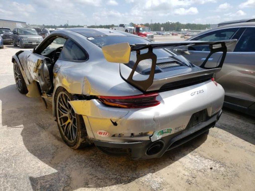 Wrecked Porsche supercar sitting in a junk yard