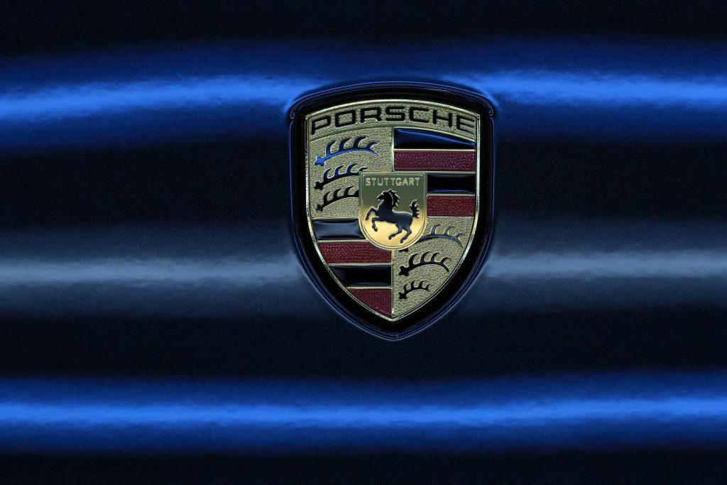Classic Porsche logo against a black and blue background