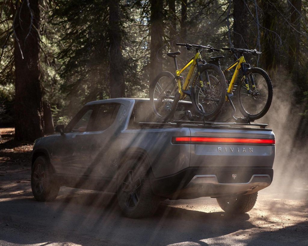 Rivian R1T electric pickup truck parked in the woods with a bike on the back