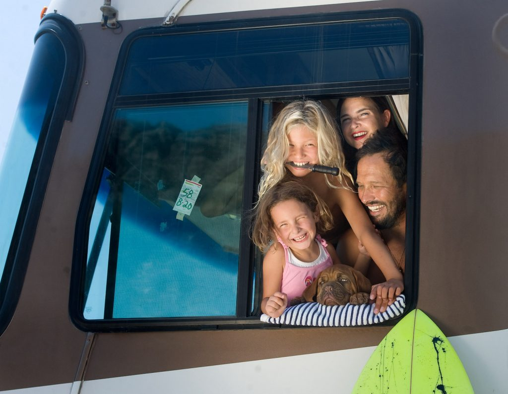 A man and woman RVing with their kids and a small brown dog