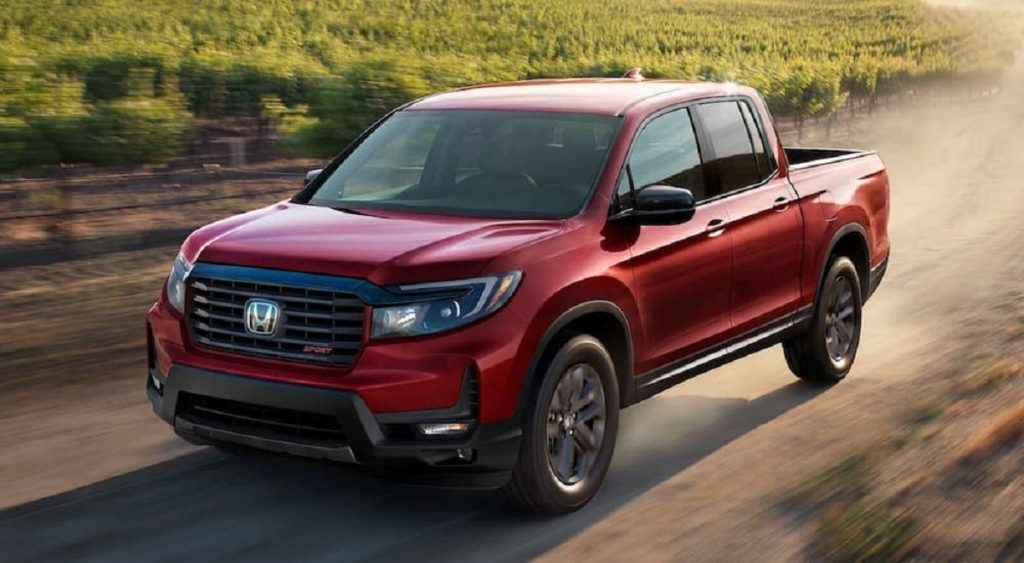 A red 2021 Honda Ridgeline races down a dirt road. Consumer Reports ratings make the Ridgeline a great choice.