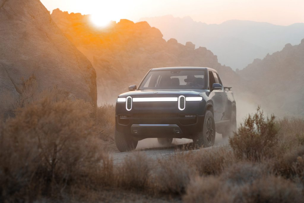 Rivian electric truck parked in a hazy desert. The Rivian R1T will be many people's first EV.