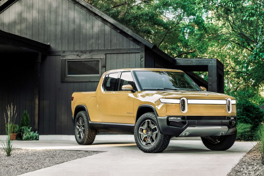 A yellow Rivian R1T parked in front of a house in the forest