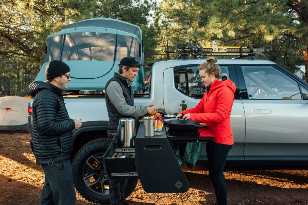 Campers next to a silver Rivian R1T with a bed-mounted tent and a slide-out camp kitchen