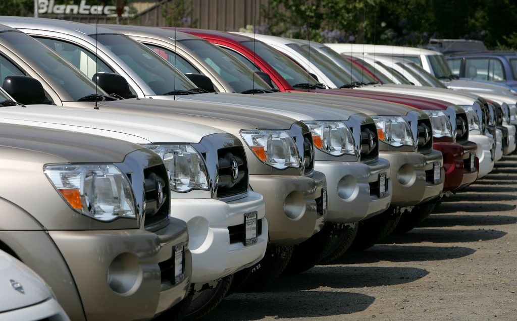 A row of pickup trucks on a dealership lot. Pickup trucks are safer than cars due to their weight and size.