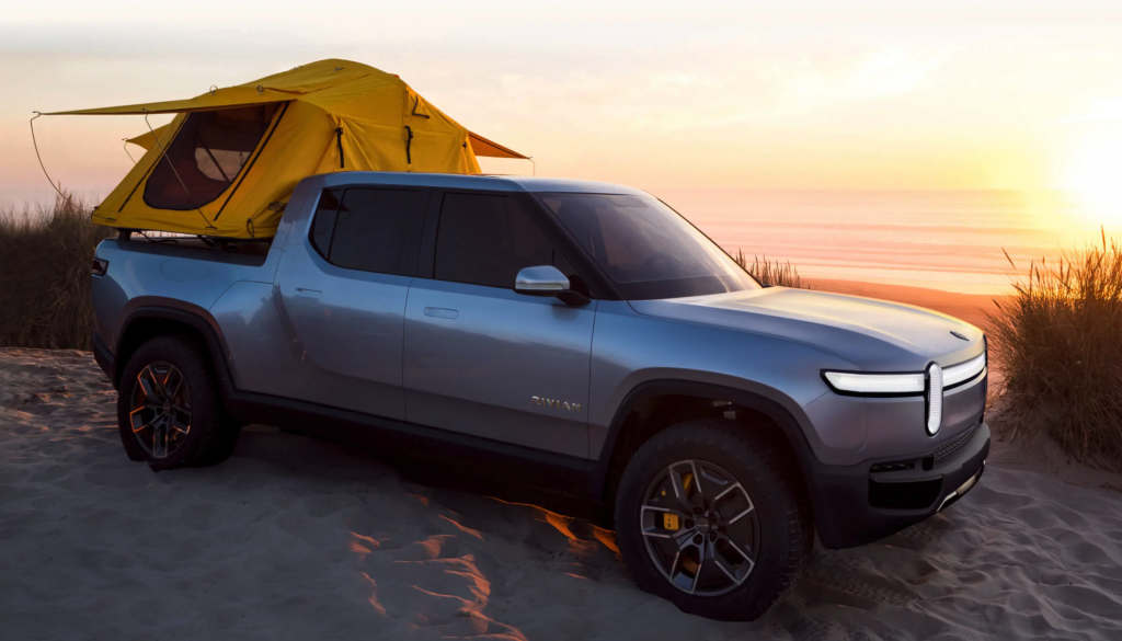 The 2021 Rivian R1T parked on the beach with a yellow tent on the back
