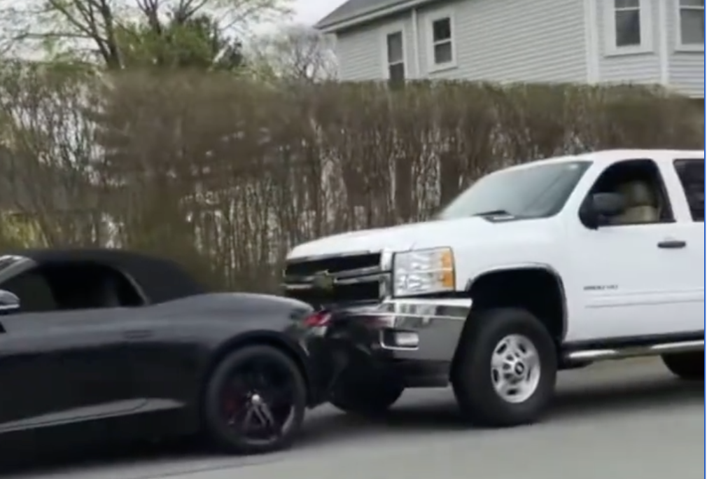 An iamge of a Jaguar F-Type falling from a trailer and crashing into a pickup truck.