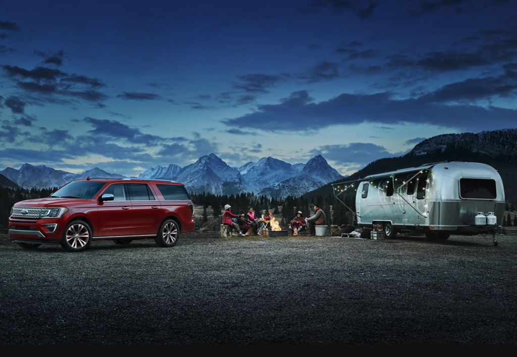 A red 2021 Ford Expedition parked at a campsite with an Airstream trailer