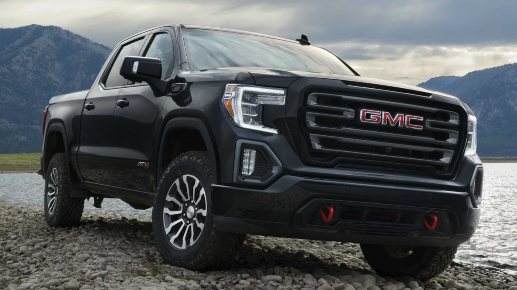 A black 2021 GMC Sierra AT4 parked in gravel in front of a lake