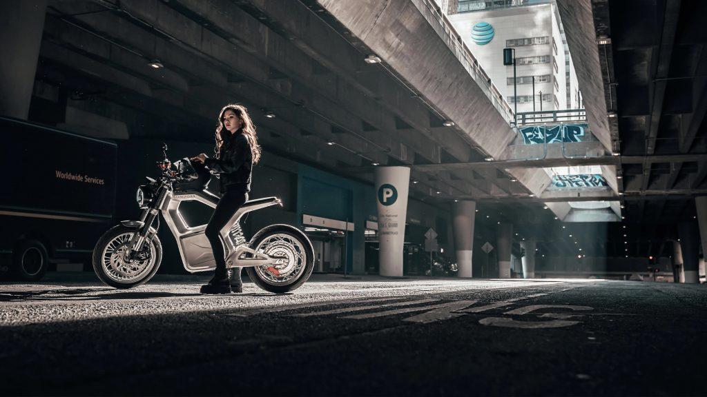 A black-clad rider on a silver Sondors Metacycle on a city street underneath a bridge