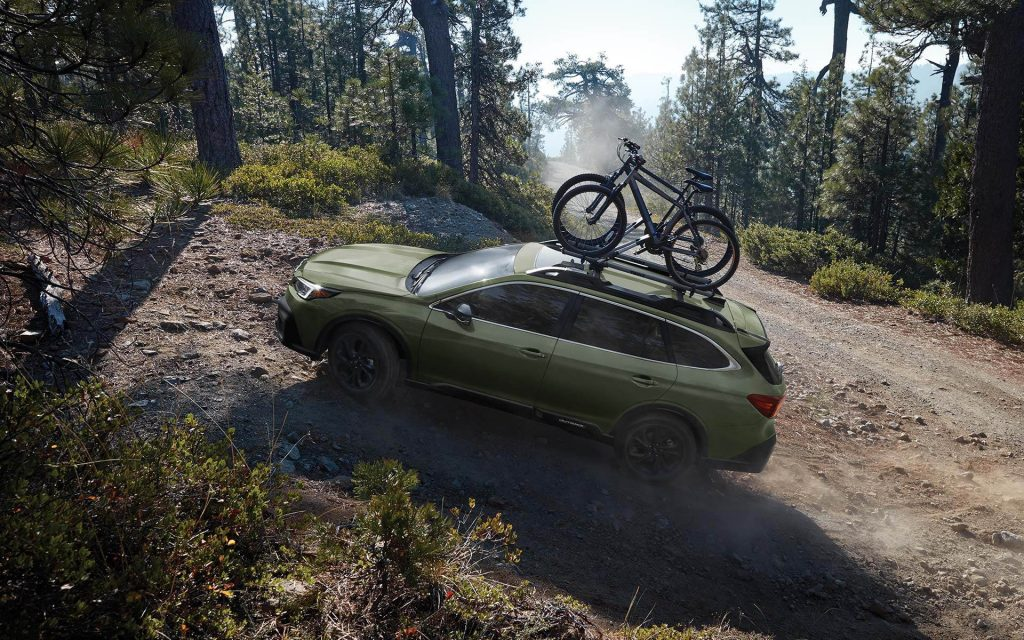 a green subaru outback with bikes on top climbing a forested hill