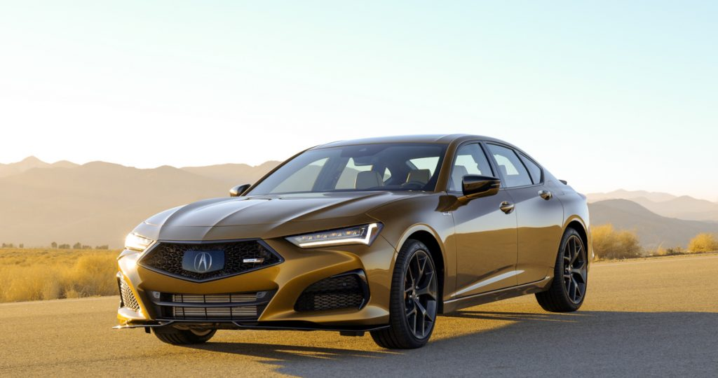 A gold Acura TLX Type S sits on tarmac at sunset