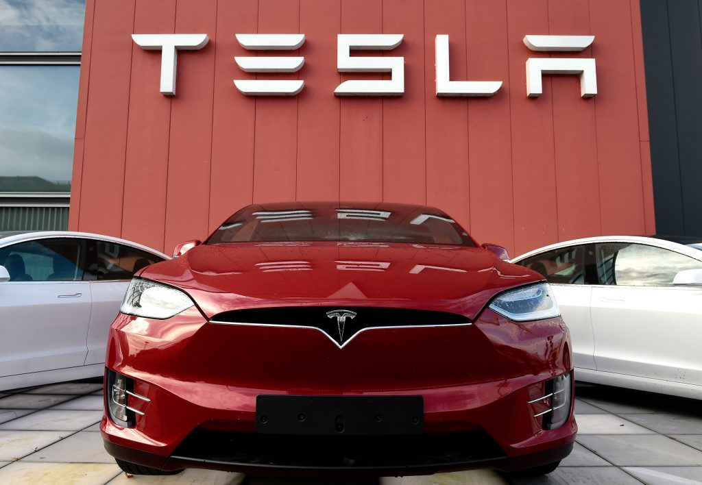 A red Tesla sits on a showroom floor.