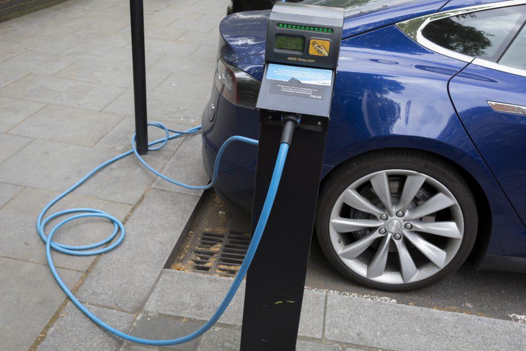 A blue Tesla Model S charging