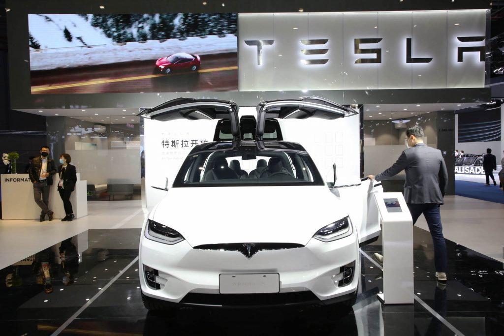 A visitor experiences a white Tesla Model X during the 3rd China International Import Expo (CIIE) at the National Exhibition and Convention Center