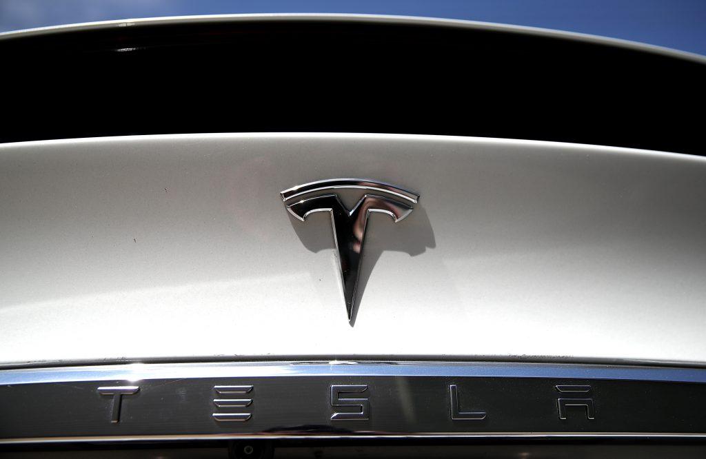 Silver Tesla logo badge on a white Model S