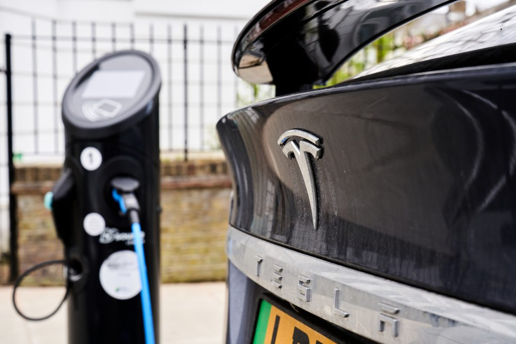 A Tesla plugged in at a charging station, multiple Tesla models are among the best-selling EVs