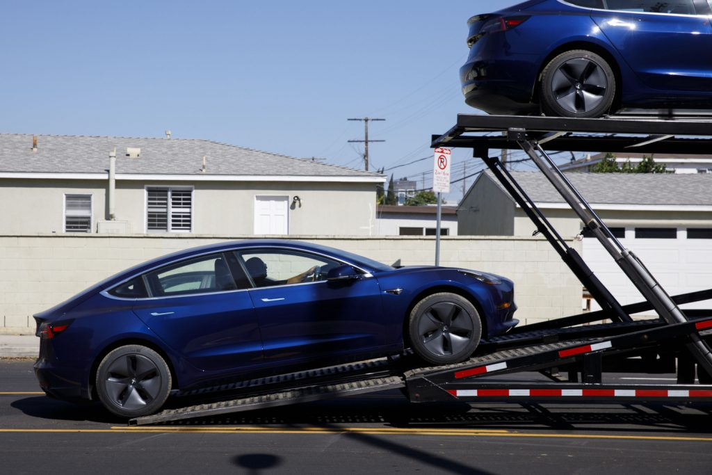 A Tesla Model 3 being loaded onto a car carried