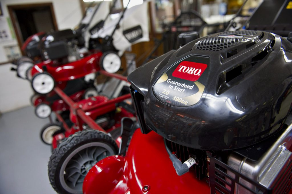 A lineup of red Toro lawn mowers, the Toro Timemaster 21199 is among the best gas push mowers