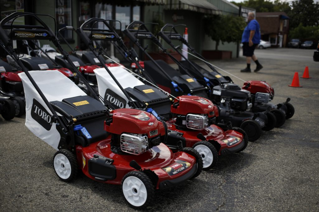 A lineup of red Toro push lawn mowers, a brand recommended by Consumer Reports for mowing small yards