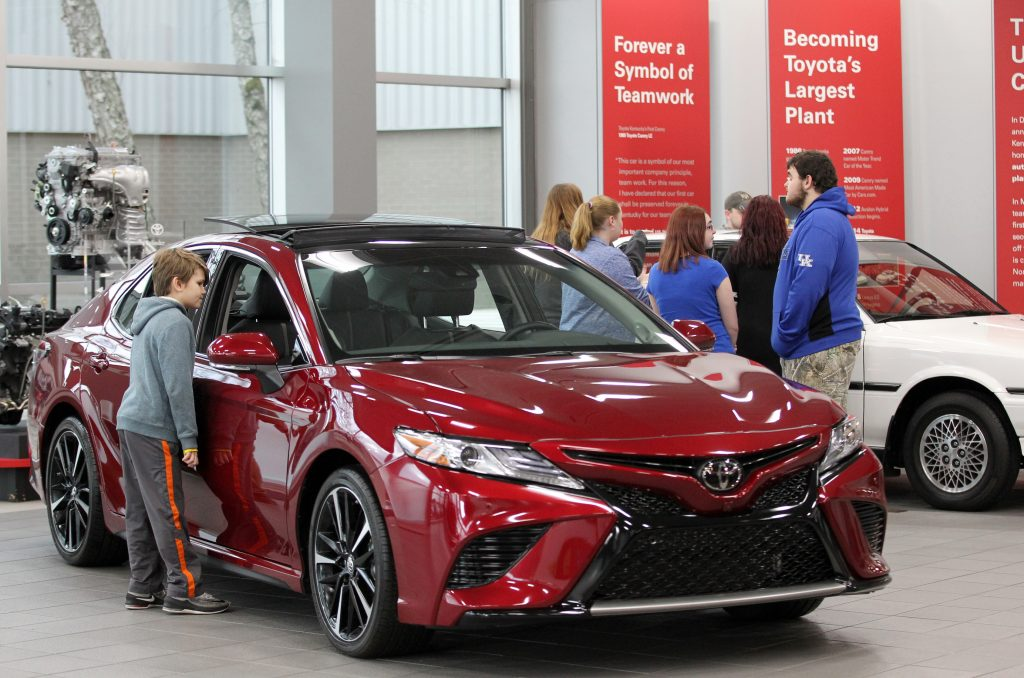 Visitors to the Toyota Motor Manufacturing plant look over the red 2019 Toyota Camry at the Georgetown plant