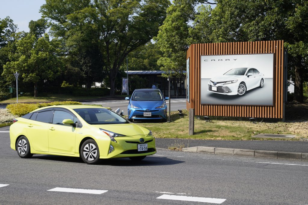 A blue Toyota Motor Corp's Prius vehicle drives past the company's Tsutsumi plant in Toyota City, Aichi Prefecture, Japan