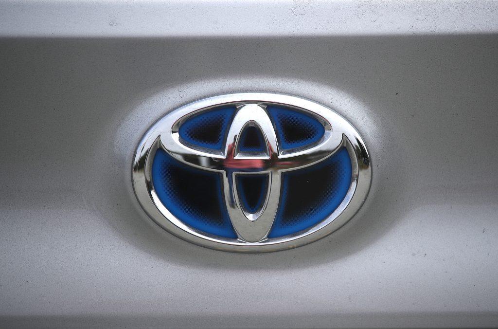 A blue and chrome Toyota emblem on a silver vehicle