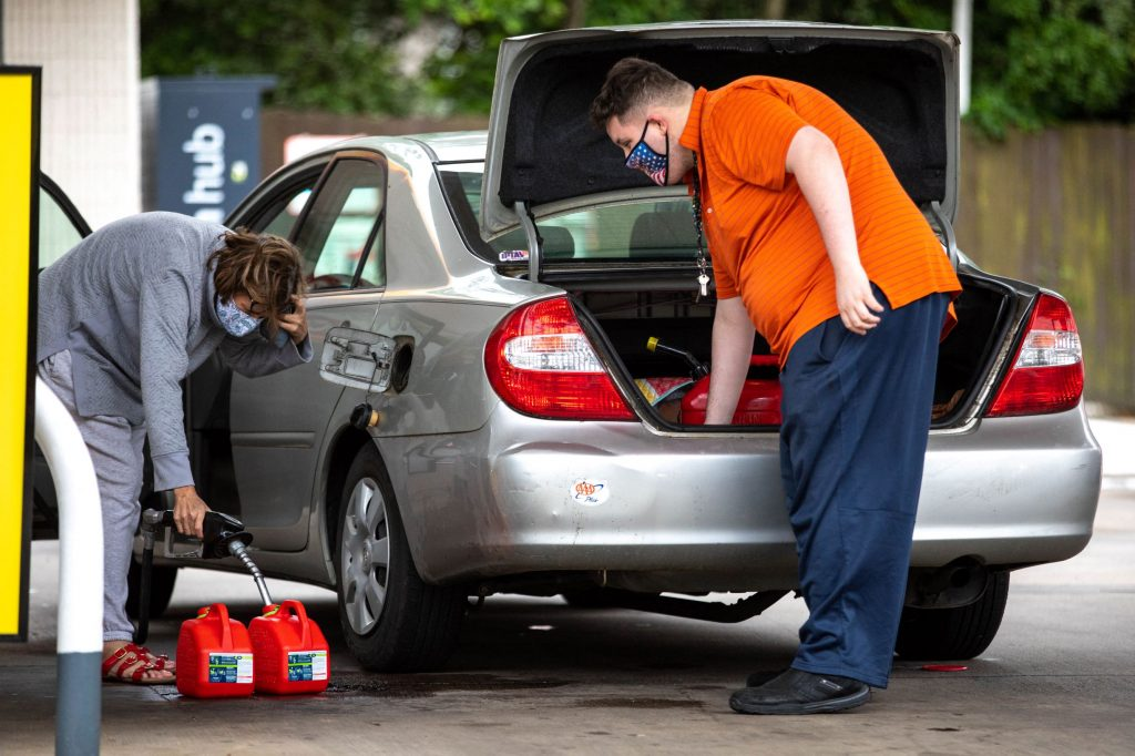 Two motorists fill up multiple gas cans and put them in their car