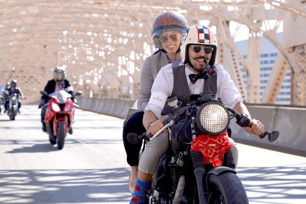 Two riders dressed in vintage clothing ride over a NYC bridge at the 2018 Distinguished Gentleman's Ride
