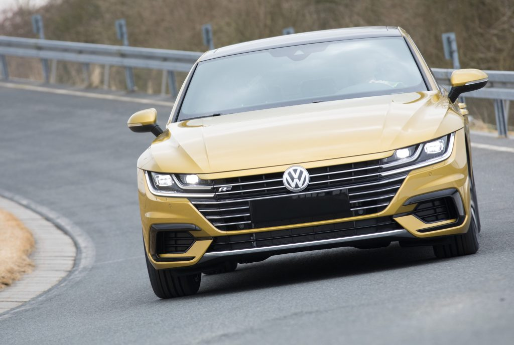 A gold VW Arteon performs a test drive near a Volkswagen manufacturing plant.