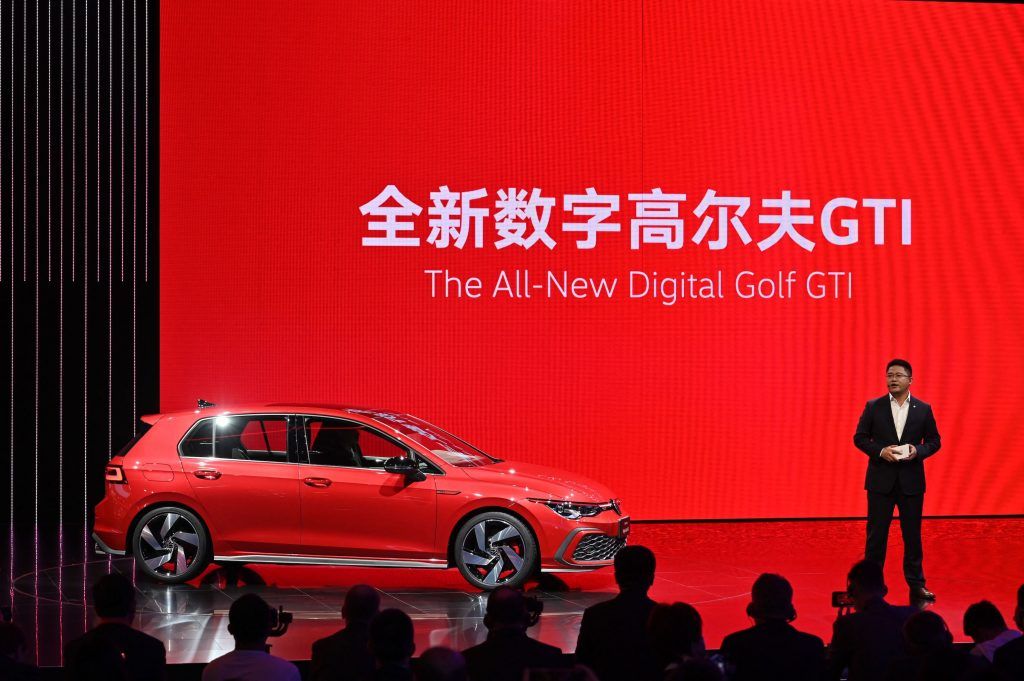 Guo Yongfeng, President of Faw-Volkswagen Sales, presents the new red Volkswagen Golf GTI car during the 19th Shanghai International Automobile Industry Exhibition in Shanghai