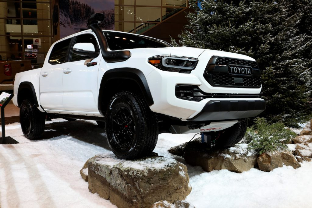 A white Toyota Tacoma pictured at an auto show.